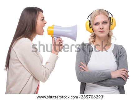 Young woman shouts at the woman in a megaphone. Another woman with headphones while she screams. White background. - stock photo