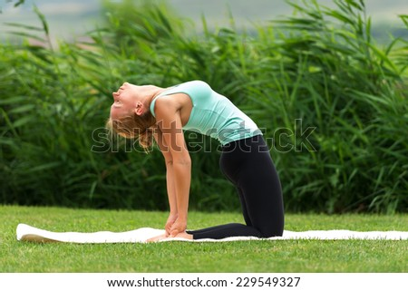 Young woman show camel yoga pose - stock photo