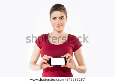 Young woman show display of mobile cell phone with white screen and smiling on a white background. - stock photo