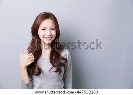 Young woman show thumb up and wearing jeans and with isolated gray background,asian - stock photo