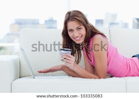 Young woman showing a beaming smile while holding a grey credit card - stock photo