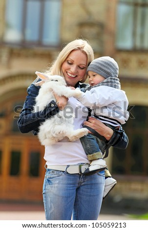 Young woman showing a fancy rabbit to her son outdoors - stock photo