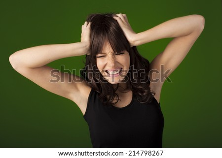 Young woman showing her anger towards someone over a green screen that can be replaced by any background. - stock photo