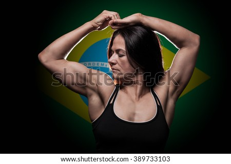 Young woman showing her muscles - with the Brazilian flag in the background - stock photo