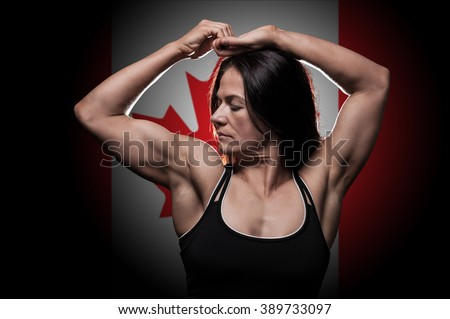 Young woman showing her muscles - with the Canadian flag in the background - stock photo