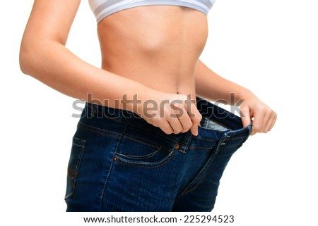 young woman showing how much weight she lost, isolated, on white background, - stock photo
