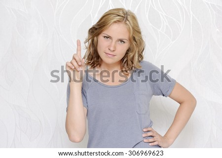Young woman showing index finger - stock photo