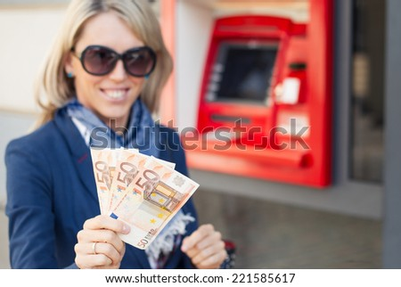 Young woman showing money after withdrawal from ATM - stock photo