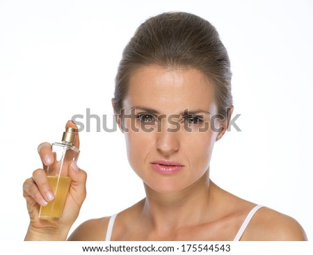 Young woman showing perfume bottle - stock photo