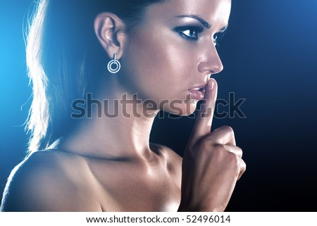 Young woman showing quiet handsign. On dark background. - stock photo