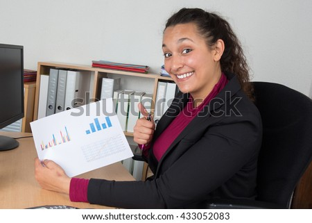 Young woman showing results, success with thumb up - stock photo