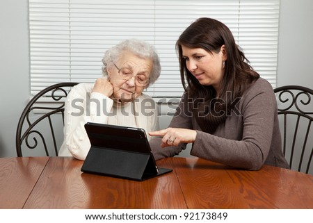 Young Woman Showing Senior Woman How to Use a Tablet PC - stock photo
