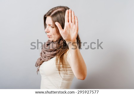 Young woman showing stop. On a gray background. - stock photo