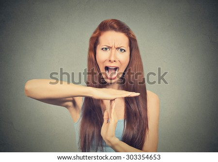 Young woman showing time out hand gesture, frustrated screaming to stop isolated on grey wall background. Too many things to do. Human emotions face expression reaction - stock photo