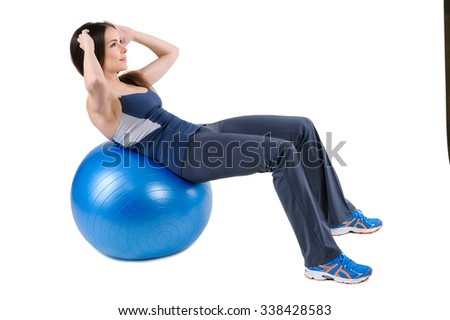 Young woman shows finishing position of Abdominal Fitball Workout, isolated on white - stock photo