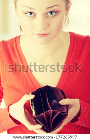 Young woman shows her empty wallet - stock photo