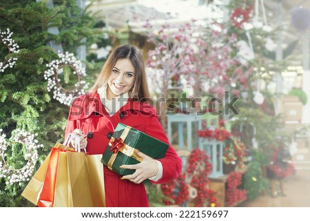 Young woman shows her gift packs inside a Christmas shop - stock photo