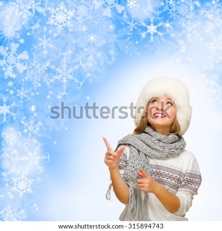 Young woman shows pointing gesture on blue snowy background - stock photo