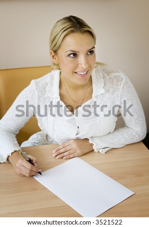 Young woman signing a blank document - stock photo