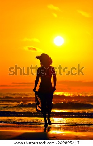 young woman silhouette on the beach in summer sunset light - stock photo