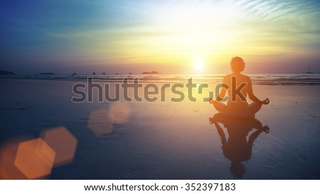 Young woman silhouette practicing yoga on the beach at amazing sunset. - stock photo