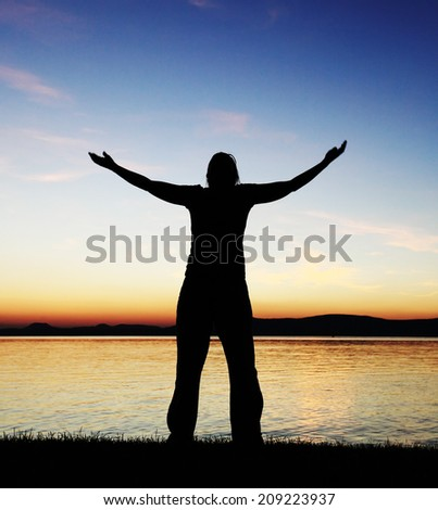 Young woman silhouette raised hands standing at coast - stock photo