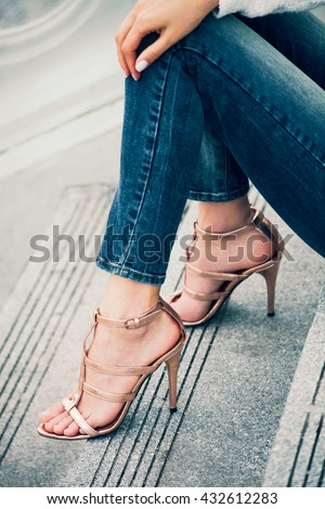 young woman sit on stairs in high heel golden sandals outdoor shot in the city - stock photo