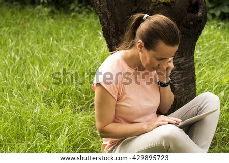 Young woman siting in park using tablet and smart phone - stock photo