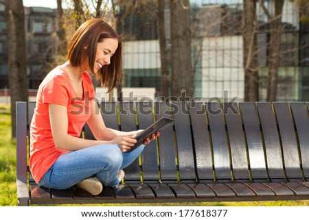 Young woman sits in a park on a wooden bench and using tablet PC - stock photo