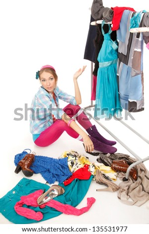 Young woman sits near her clothes rack with lots of dresses,and some clothes is on the floor - stock photo