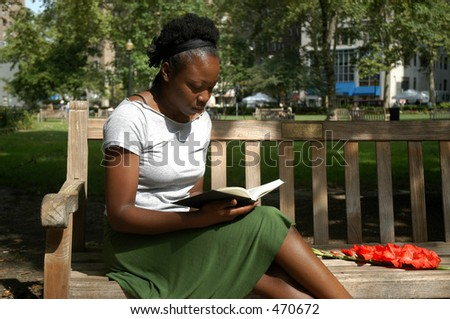 Young woman sits on a bench in a park and reads. - stock photo