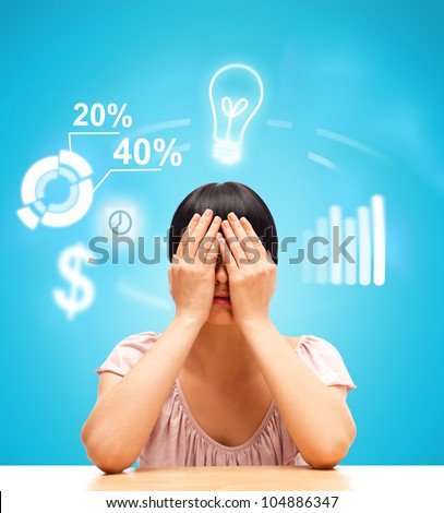 Young woman sitting against blue background with eyes closed by her hands. Business icons are flying around her head - stock photo