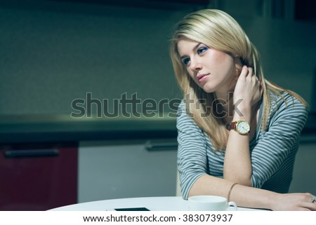 Young woman sitting alone and waiting by the phone on a night kitchen - stock photo