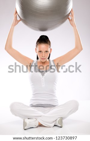 Young woman sitting and holding fitness ball above her head - stock photo