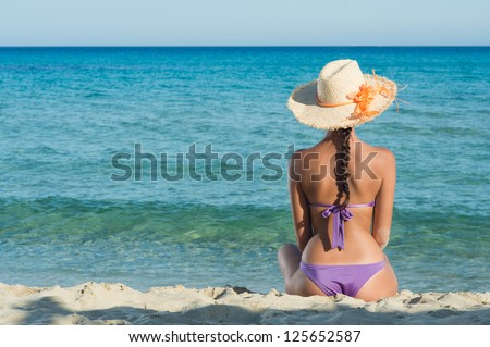 Young Woman Sitting And Looking At Sea - stock photo