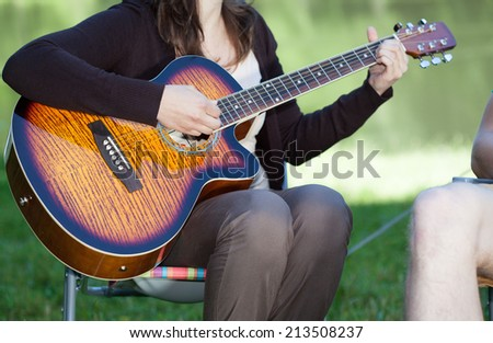 Young woman sitting and playing guitar outdoors - stock photo