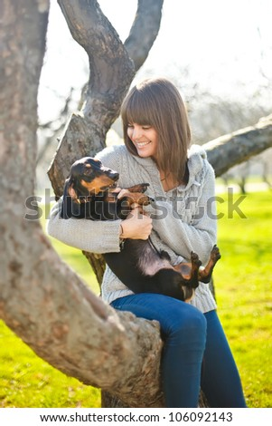 young woman sitting and playing with badger-dog in a park - stock photo