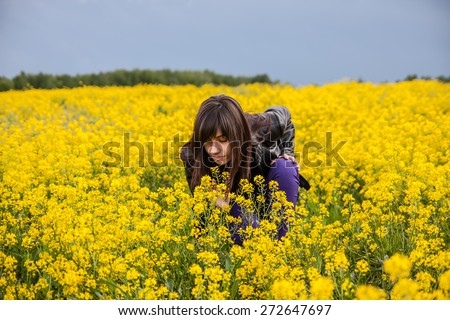 Young woman sitting and smelling the flower on the blossom mustard field. Full of yellow flowers. - stock photo