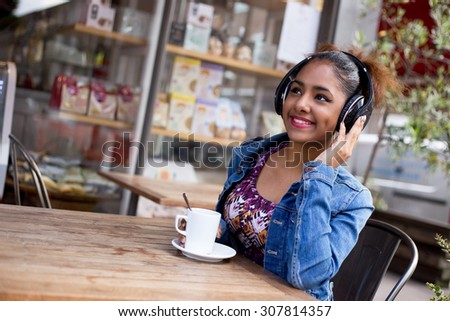 young woman sitting at a coffee shop listening to music. - stock photo