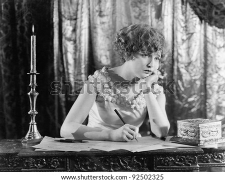Young woman sitting at a desk with a pen in hand, looking sad while writing a letter - stock photo