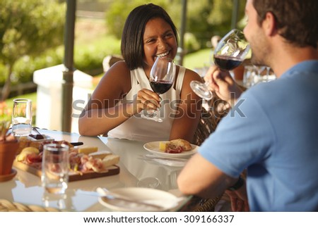 Young woman sitting at a table with her boyfriend drinking red wine. Happy young couple at wine bar restaurant. - stock photo