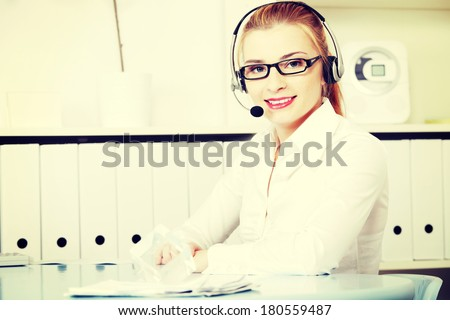 Young woman sitting at desk in office with headphones set working in call center. Blond secretary/receptionist in glasses and white shirt talking through microphone as help desk consultant. - stock photo