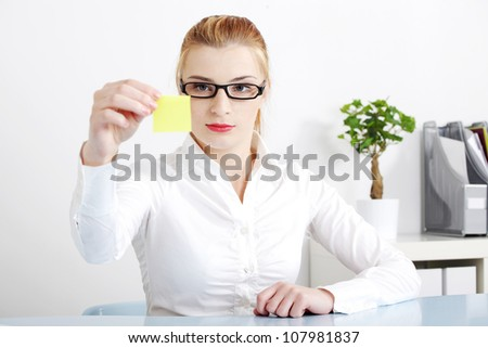 Young woman sitting at desk in office with yellow post-it sticker in her hand. Blond businesswoman in glasses and white shirt looking at the paper with important information to remember. - stock photo