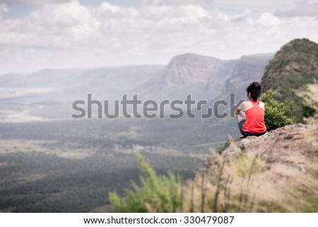 Young woman sitting at edge of cliff looking over expansive view of plains and mountains in South Africa - stock photo