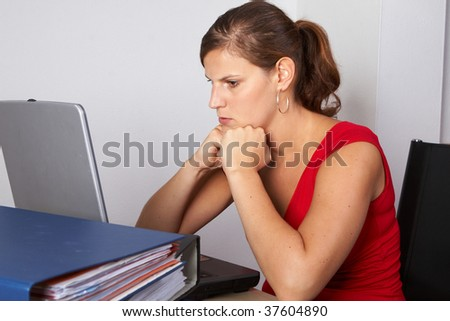 Young woman sitting at her laptop with a lot of work in front of her. She is very frustrated. - stock photo