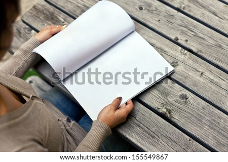 Young woman sitting at the table with a booklet with white pages. The white pages can be used for any logos, label signs or any graphic additions. - stock photo