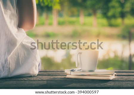 Young woman sitting beside coffee cup and notebooks on rustic wood bench with rural lake view in morning time on weekend with vintage filter effect - stock photo