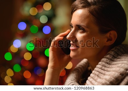 Young woman sitting chair and making phone call in front of Christmas lights - stock photo