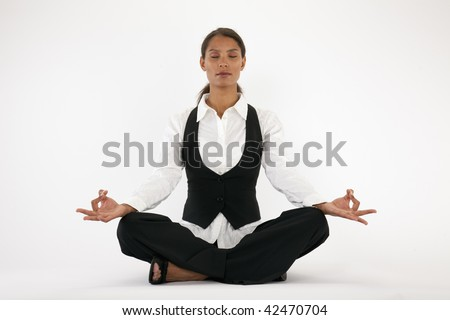 Young woman sitting cross legged and meditating. Horizontally framed shot. - stock photo