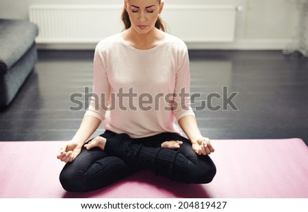 Young woman sitting cross legged on exercise mat with hands on knees meditating. Fitness female relaxing with yoga workout. - stock photo